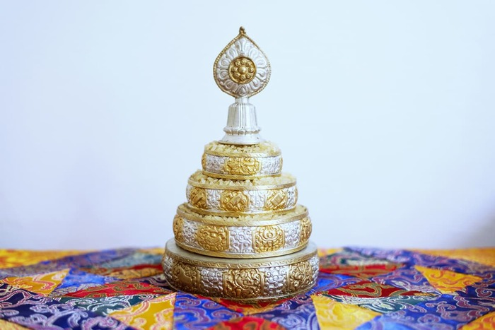 A mandala offering set filled with rice.